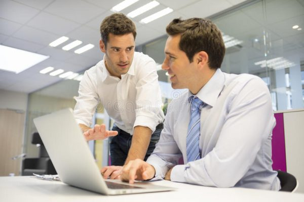two men consulting with a laptop